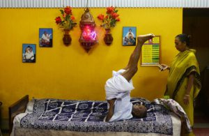 In this photograph taken on August 2, 2016, Indian monk Swami Sivananda (C), who claims to be 120 years old, is watched by one of his followers as hepractises yoga in Kolkata. An Indian monk who claims to be the oldest man to have ever lived at 120 years, says he owes his longevity to daily yoga and a life without sex or spices. Born on August 8, 1896, according to his passport, Hindu monk Swami Sivananda's life has spanned three centuries. He is now applying to Guinness World Records to stake his claim to the distinction. / AFP PHOTO / Dibyangshu SARKAR / TO GO WITH AFP STORY: ' India-Lifestyle-Oldest-Man' Feature by Dibyangshu SARKARDIBYANGSHU SARKAR/AFP/Getty Images