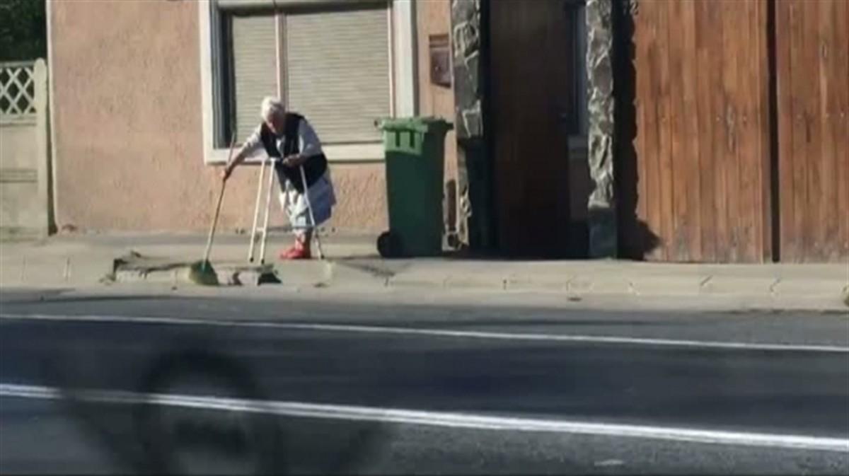 O bătrână emoționează internetul după ce a fost surprinsă în timp ce mătura trotuarul sprijinindu-se de un cadru.