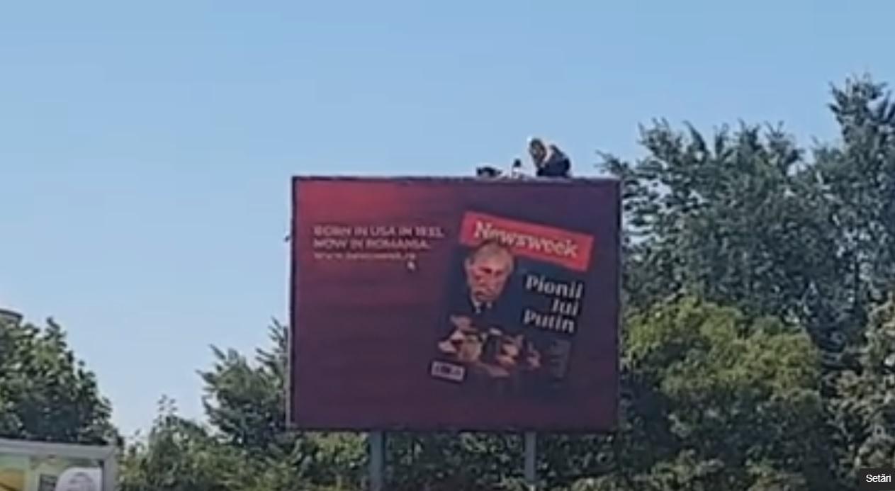 Un bărbat s-a urcat pe un panou publicitar la Piața Unirii și protestează VIDEO. Mai multe echipaje de poliție la fața locului