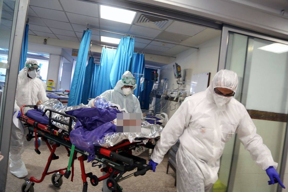Un ambulanțier poartă un combinezon prins cu bandă adezivă la un caz de coronavirus